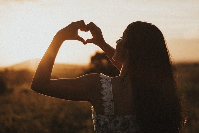 Love sign from hand at sunset - Why We Love Black Tourmaline